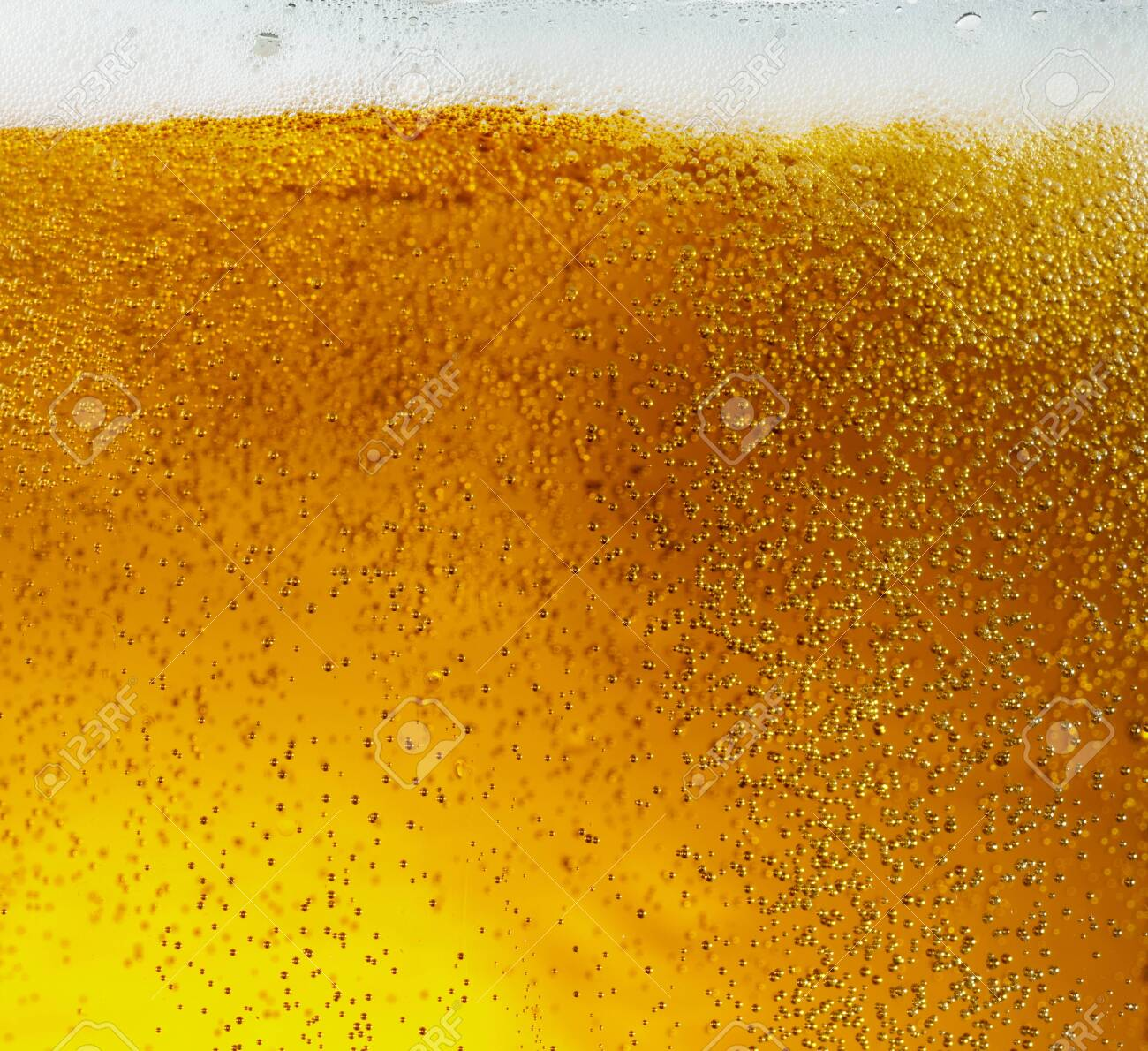 Close up view of floating bubbles in light golden colored beer - 124799651