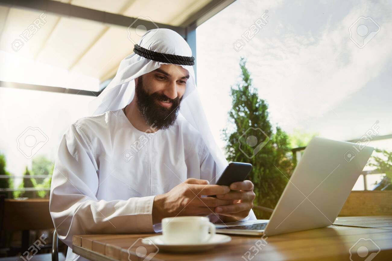 Arab saudi businessman working online with a laptop and tablet
