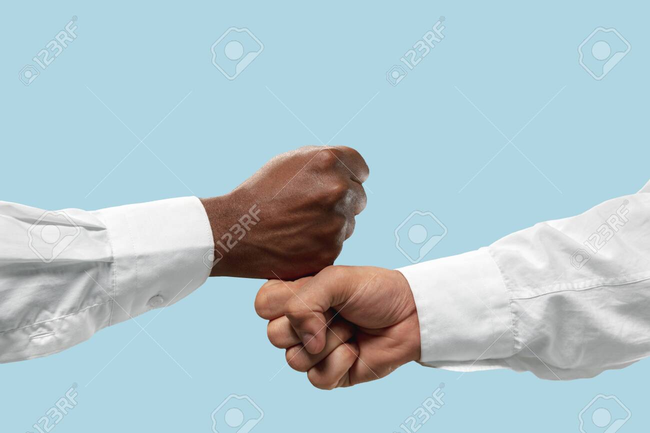 Friends greetings sign or disagreement. Two male hands competion in arm wrestling isolated on blue studio background. Concept of standoff, support, friendship, business, community, strained relations. - 125504218