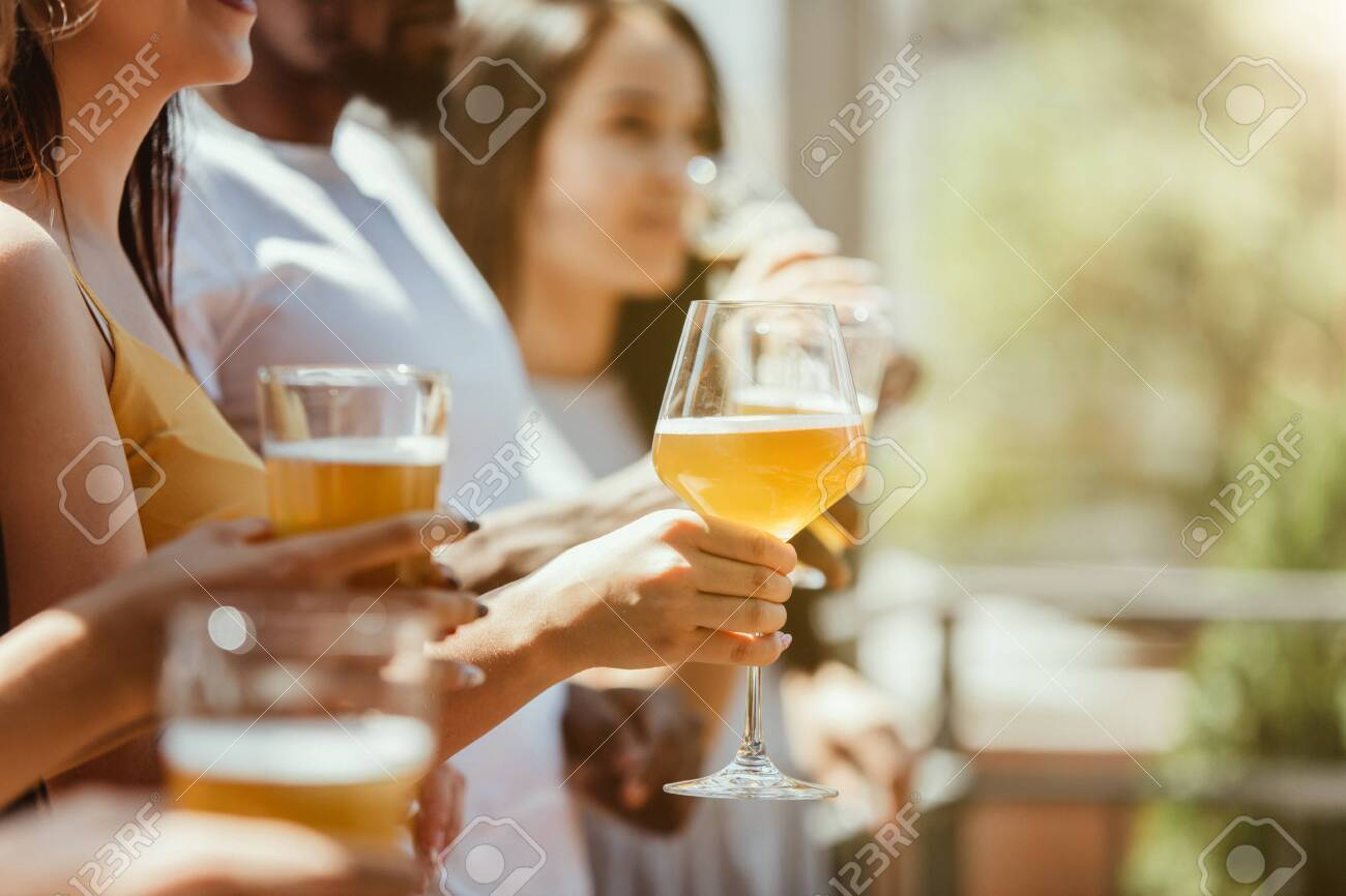 Young group of friends drinking beer, having fun, laughting and celebrating together. Women and men with beers glasses in sunny day. Oktoberfest, friendship, togetherness, happiness, summer concept. - 126877878