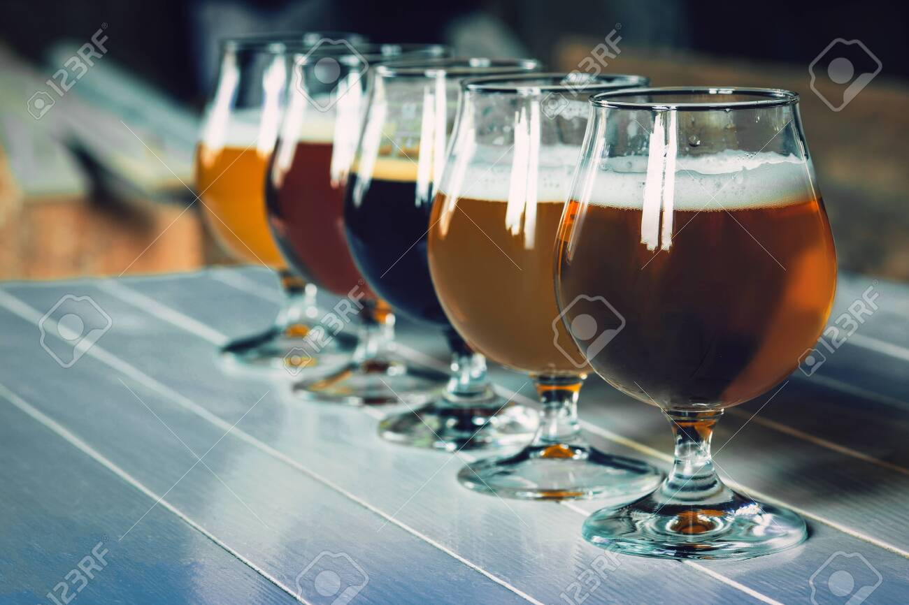 Glasses of different kinds of dark and light beer on wooden table in line. Cold delicious drinks are prepared for a big friends party. Concept of drinks, fun, meeting, oktoberfest. - 127691520