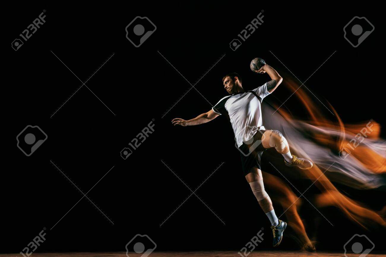 Caucasian young handball player in action and motion in mixed lights over black studio background. Fit male professional sportsman. Concept of sport, movement, energy, dynamic, healthy lifestyle. - 127782020