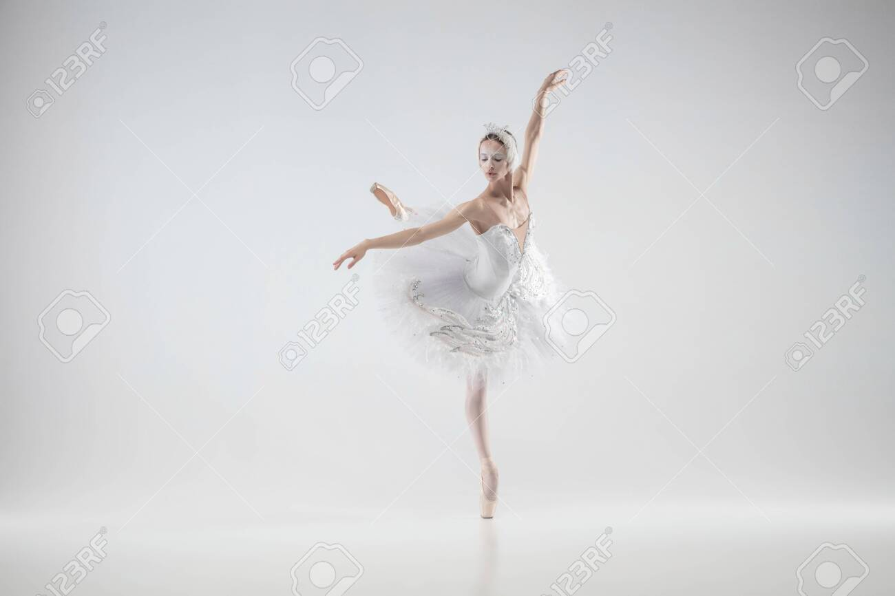 Winter alive. Young graceful classic ballerina dancing on white studio background. Woman in tender clothes like a white swan. The grace, artist, movement, action and motion concept. Looks weightless. - 140542954