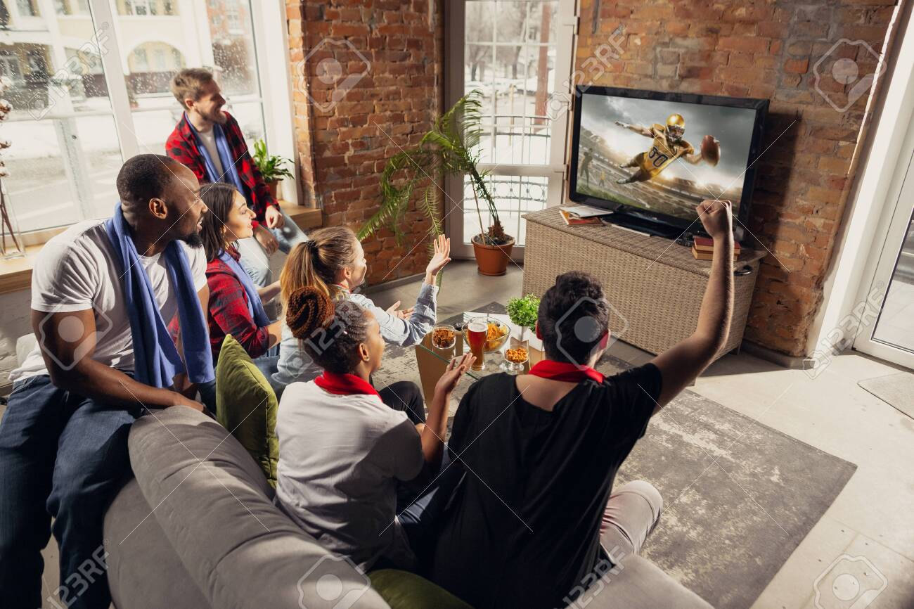 Excited group of people watching american football, sport match at home. Multiethnic group of emotional friend, fans cheering for favourite national team, drinking beer. Concept of emotions, support. - 141084947