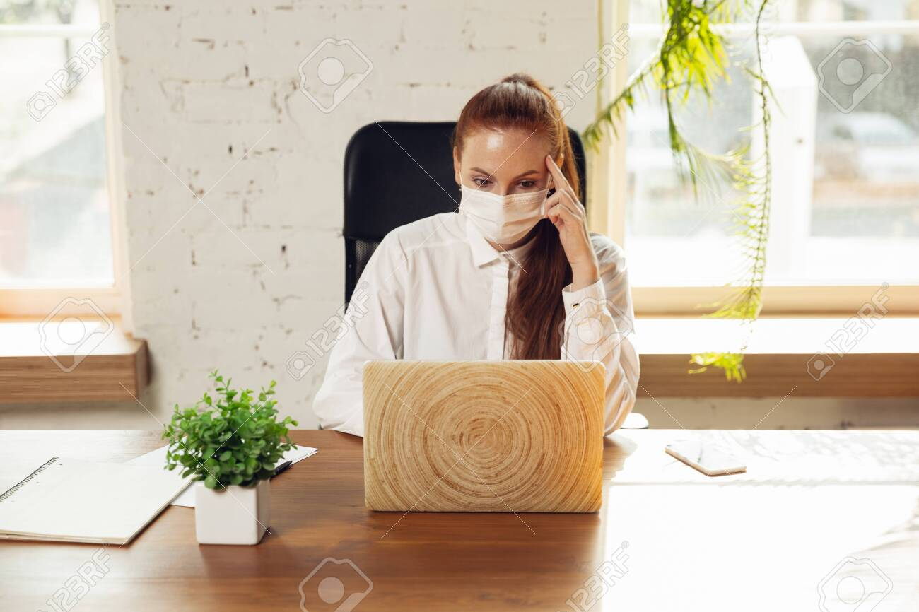 Woman working in office alone during coronavirus or COVID-19 quarantine, wearing face mask. - 144577046