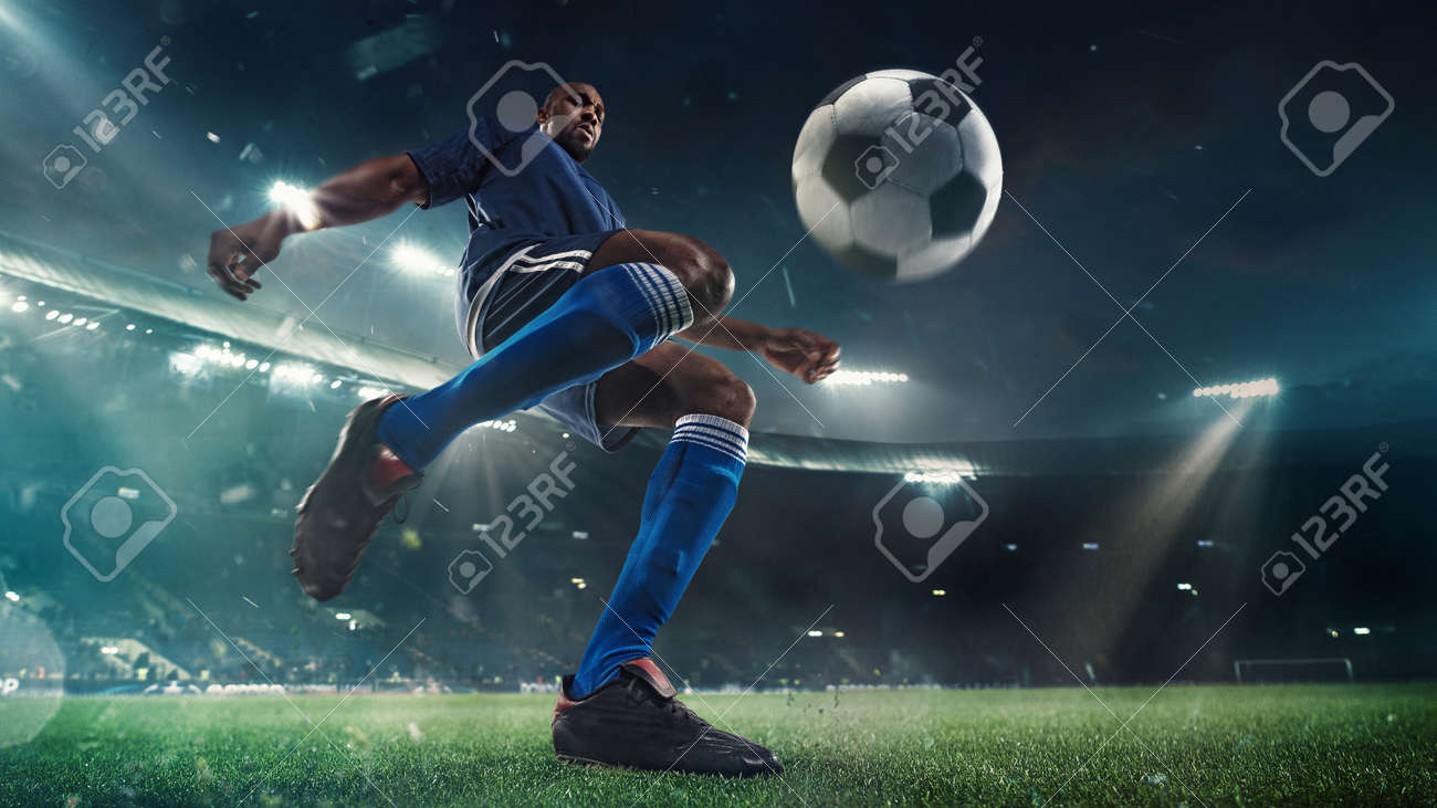 Professional football or soccer player in action on stadium with flashlights, kicking ball for winning goal, wide angle. Concept of sport, competition, motion, overcoming. Field presence effect. - 144949063