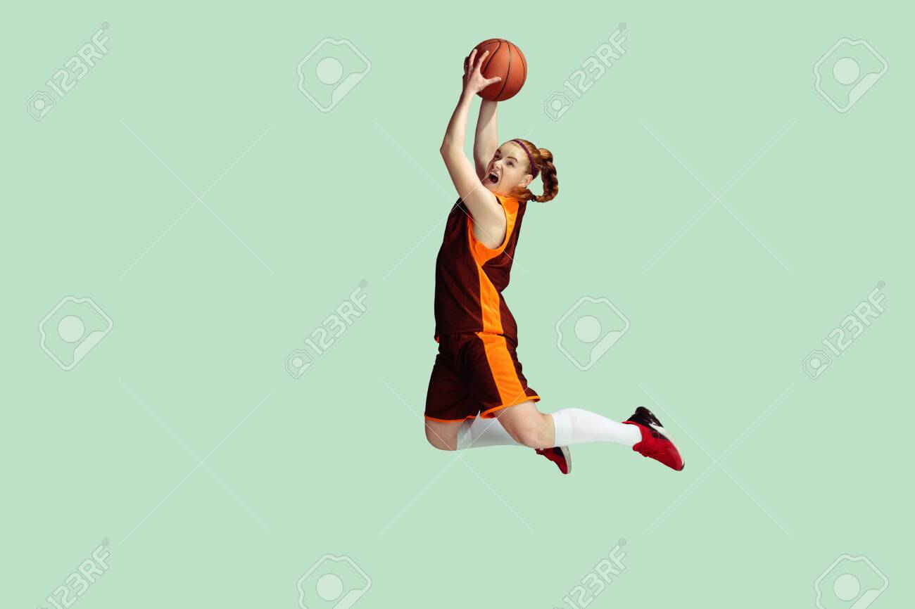 Young caucasian female basketball player in action, motion in high jump isolated on mint colored background. Concept of sport, movement, energy and dynamic, healthy lifestyle. Training, practicing. - 146904964
