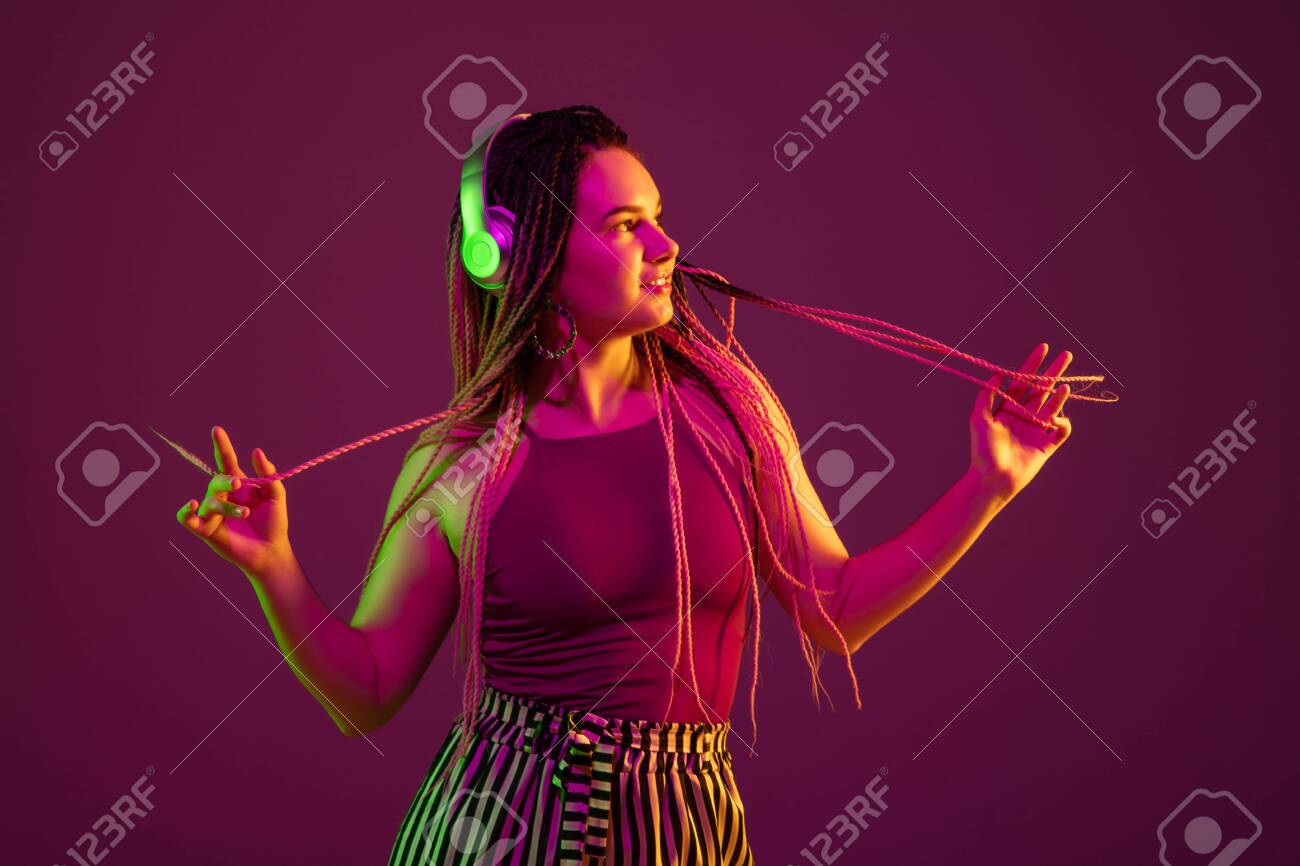 Young caucasian woman dancing with headphones on pink studio background in neon light. Beautiful model with dreadlocks. Human emotions, facial expression, sales, ad concept. Freaks culture. - 150106555