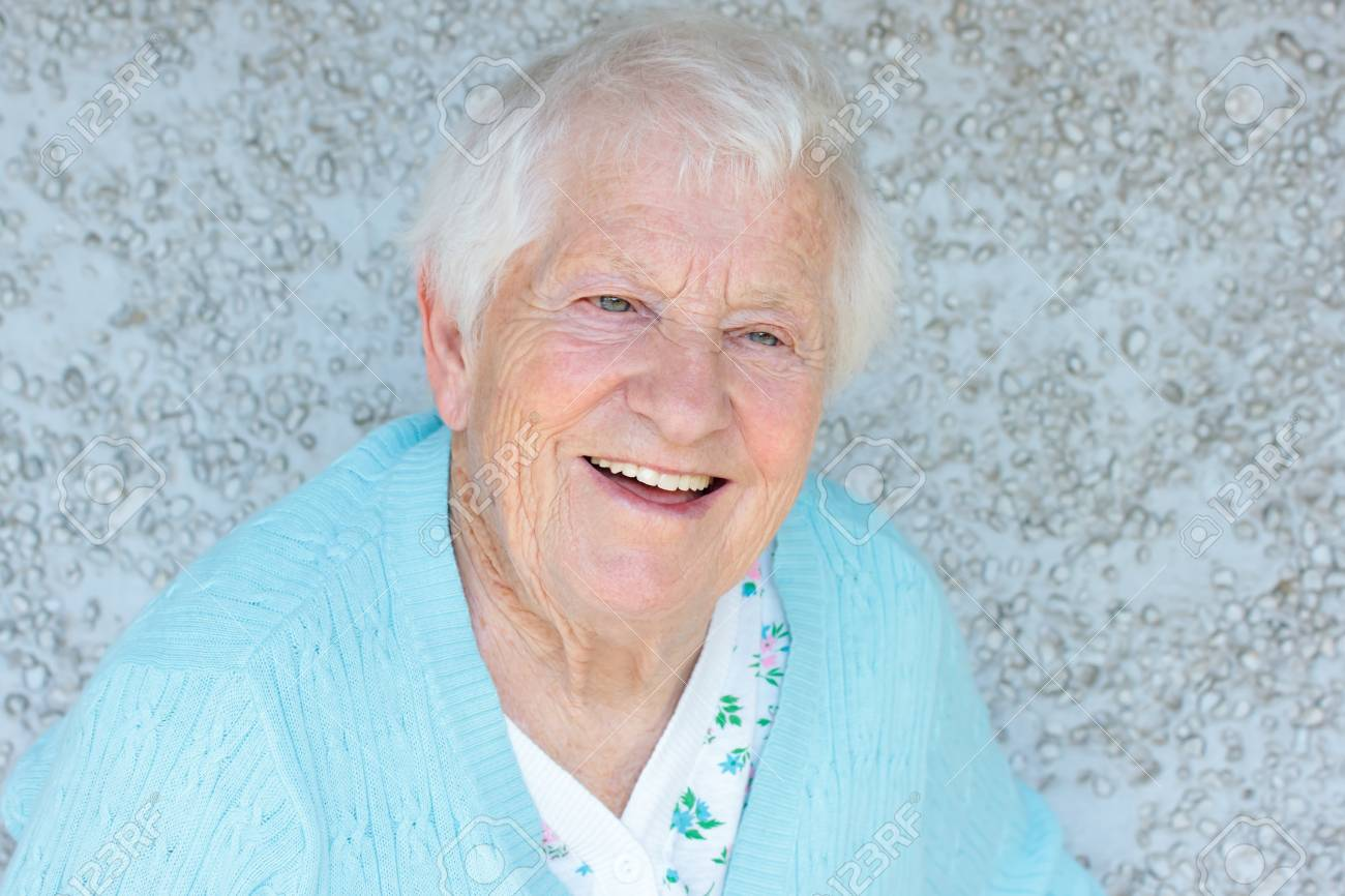 Happy senior lady smiling in front of light blue stone wall Stock Photo - 9877287