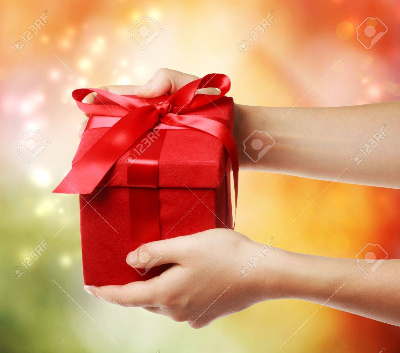 Woman holding a red gift box on a bright holiday lights background Stock Photo - 15870478