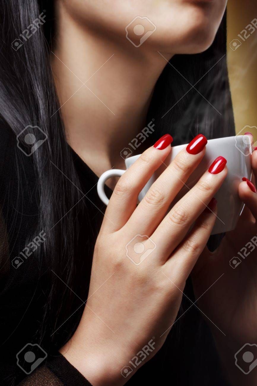Beautiful woman holding a hot beverage (coffee - tea) Stock Photo - 16766147