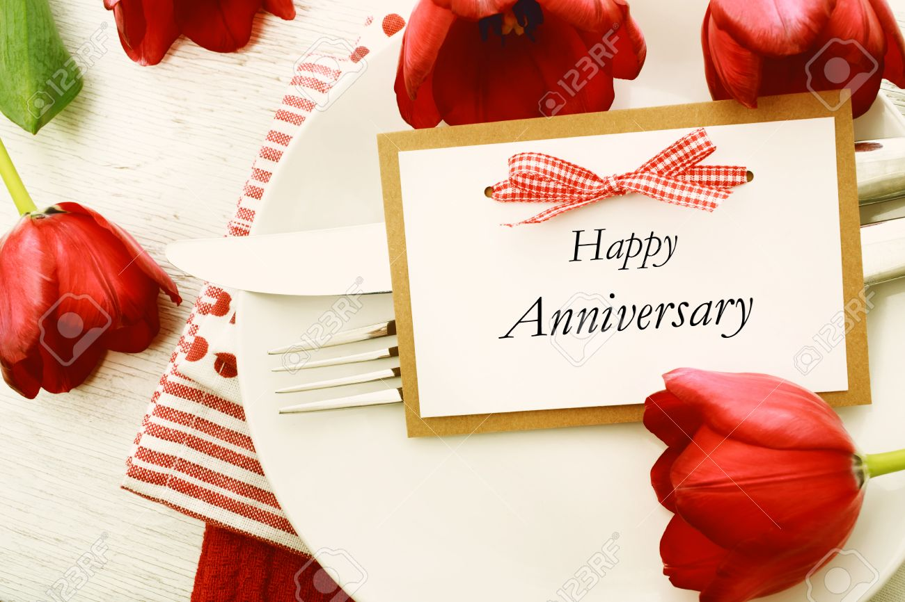 dinner table setting with happy anniversary message card and stock