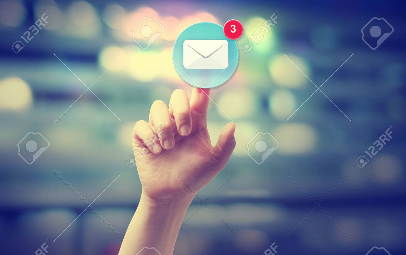 Hand pressing an email icon on blurred cityscape background - 43317885
