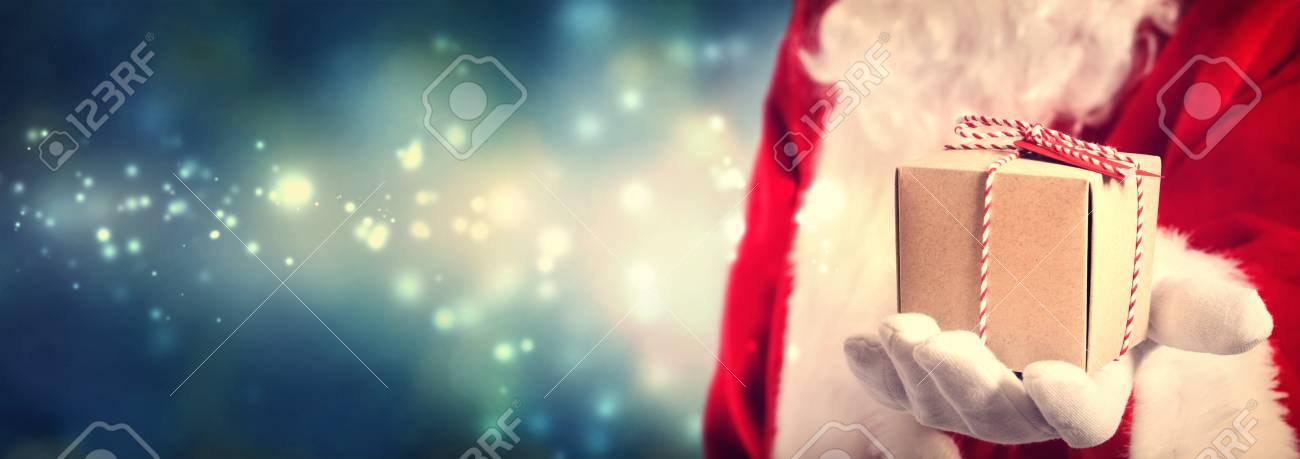 Weihnachtsmann Hält Ein Geschenk In Der Hand Lizenzfreie Fotos ...
