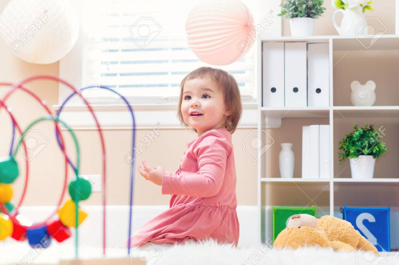 Happy toddler girl playing with toys in her house - 54659952