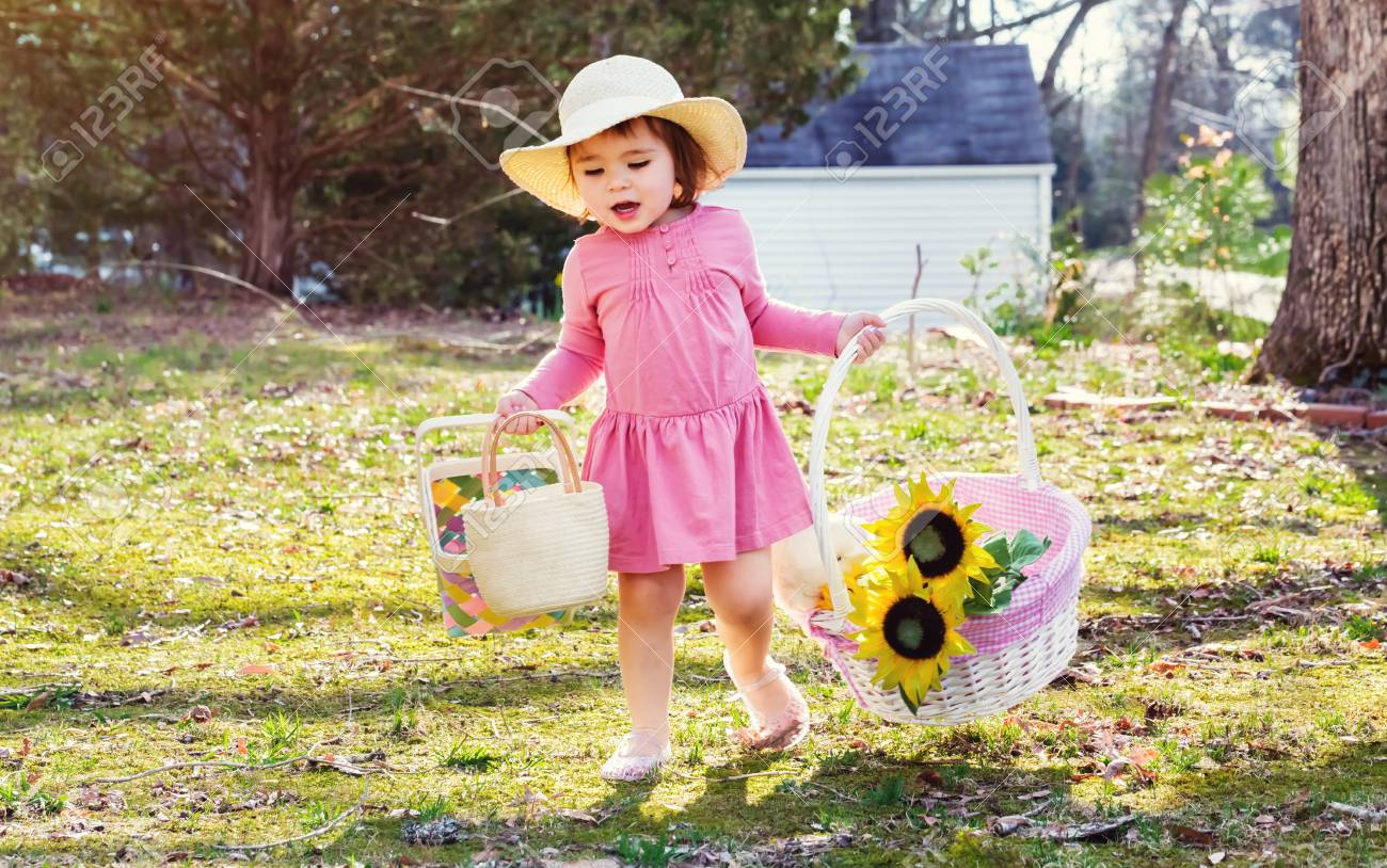 Happy Toddler Girl Playing Outside With An Easter Basket Stock Photo