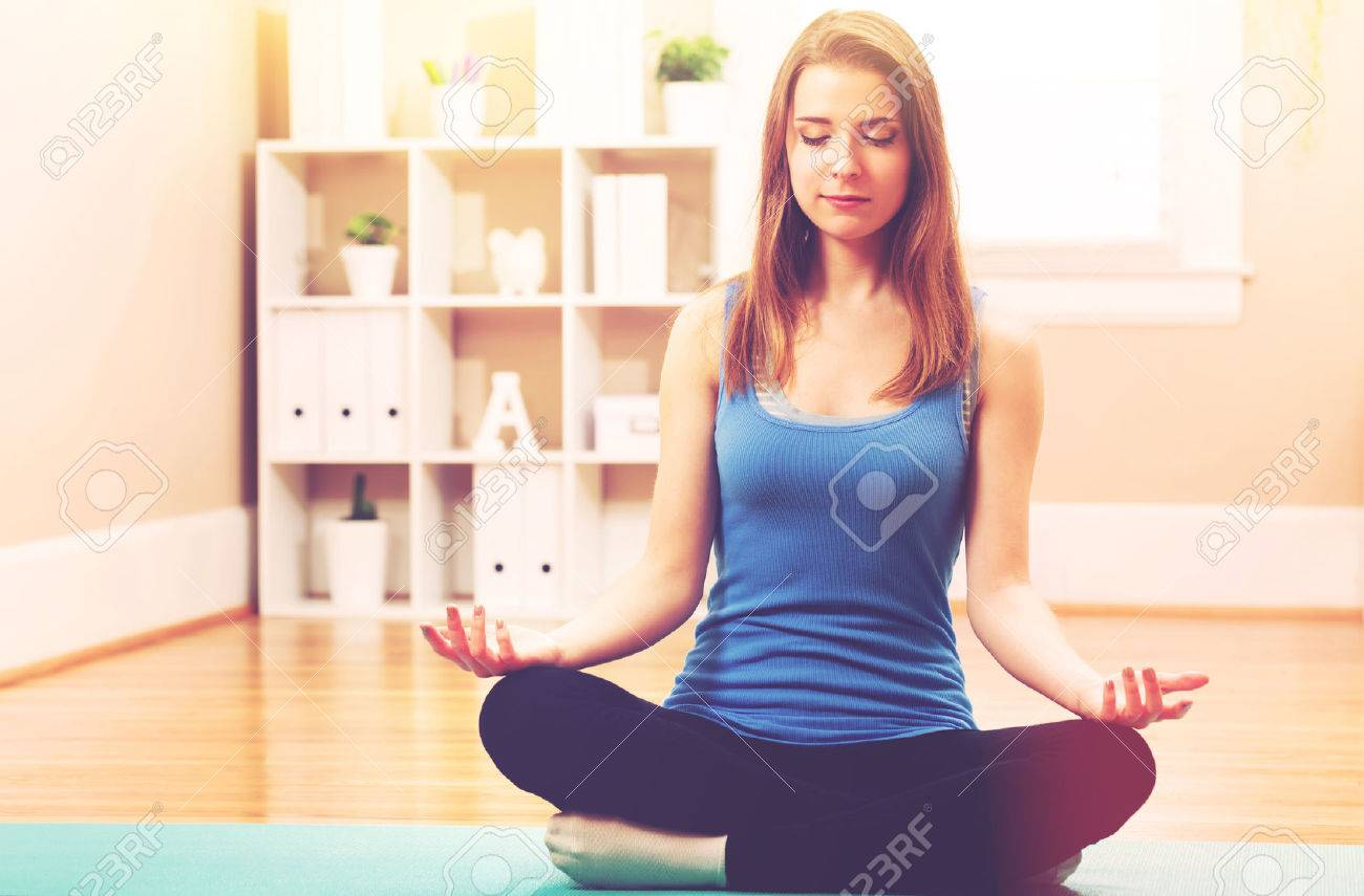 Young woman practicing meditation at home Standard-Bild - 54662598