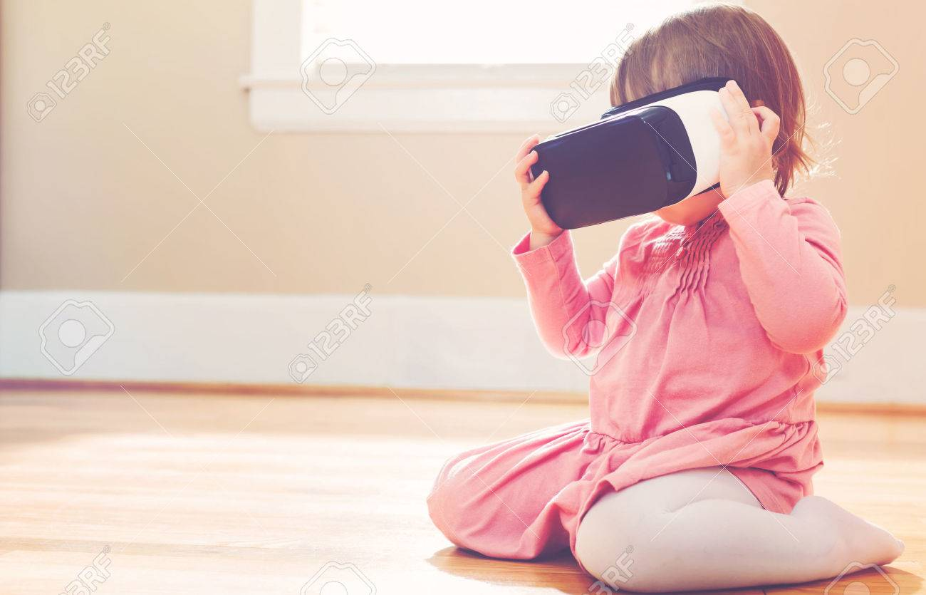 Toddler girl using a new virtual reality headset Standard-Bild - 58705615