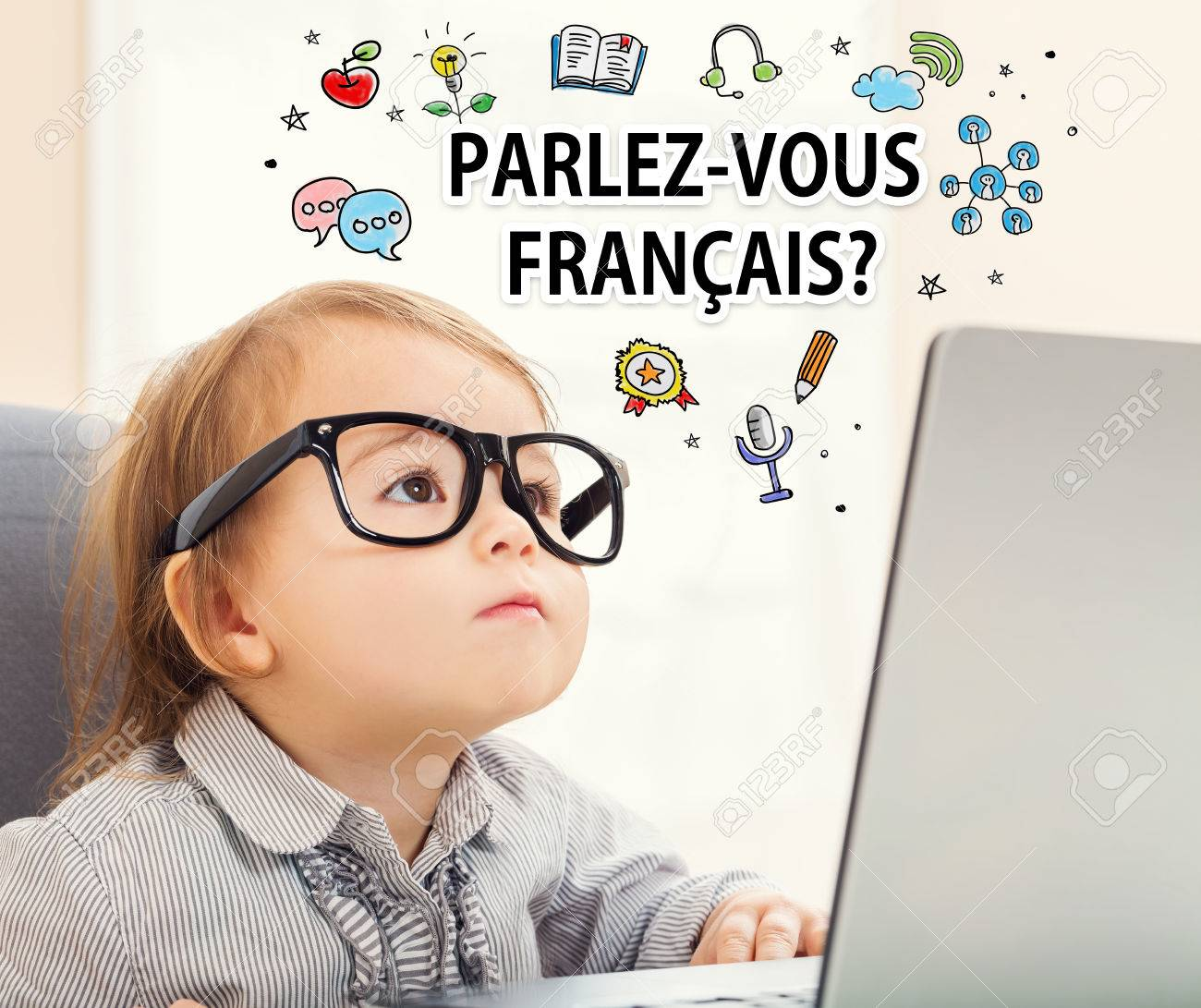 Parlez vous Francais (Do you speak French) texts with toddler girl using her laptop Standard-Bild - 59198824