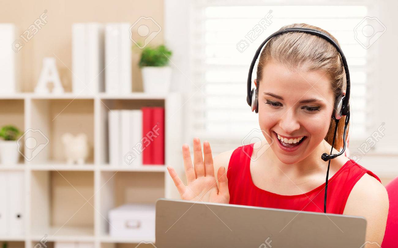 Happy young woman with headset talking on her laptop Standard-Bild - 59198877