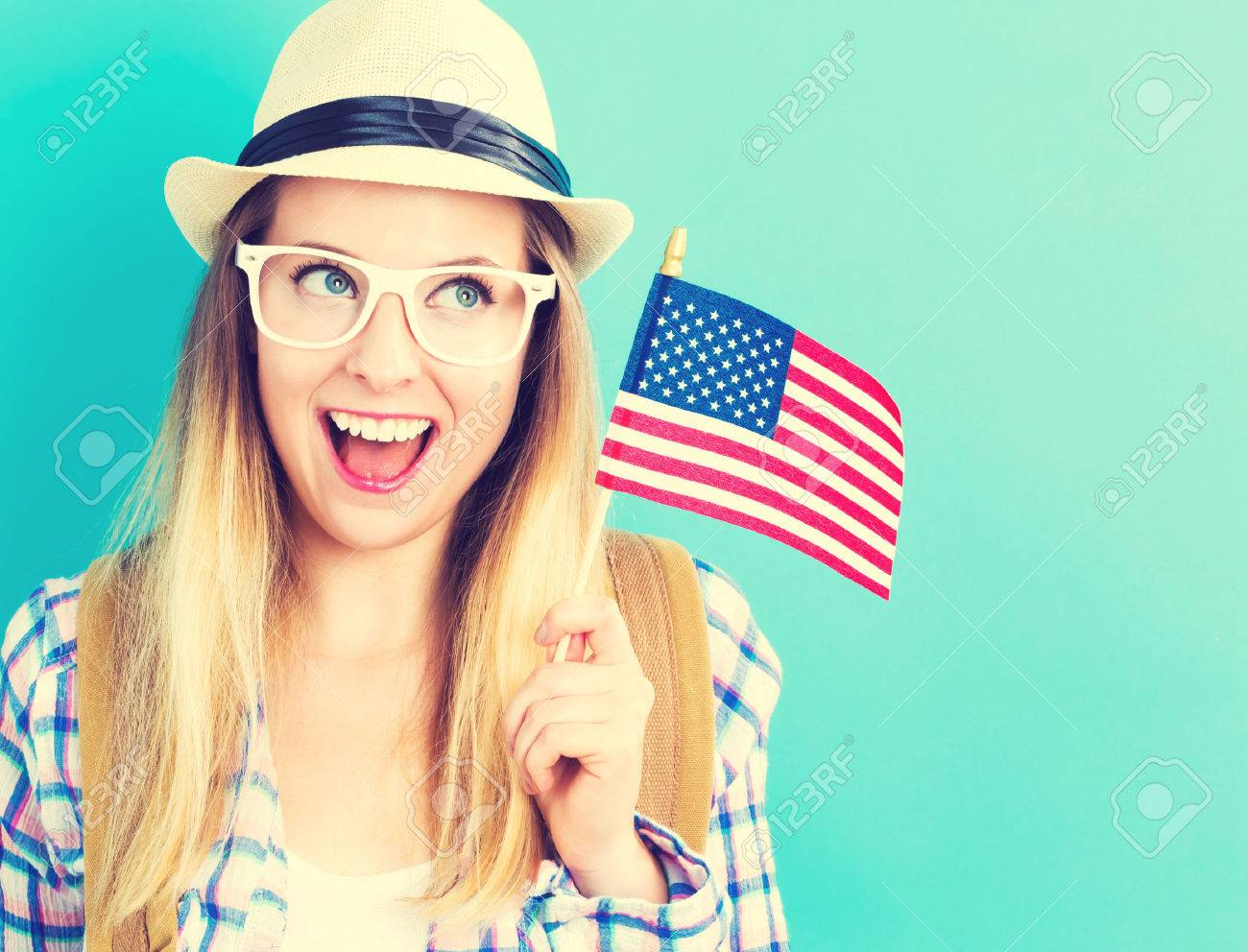 Happy young traveling woman holding American flag on blue background Standard-Bild - 60942040