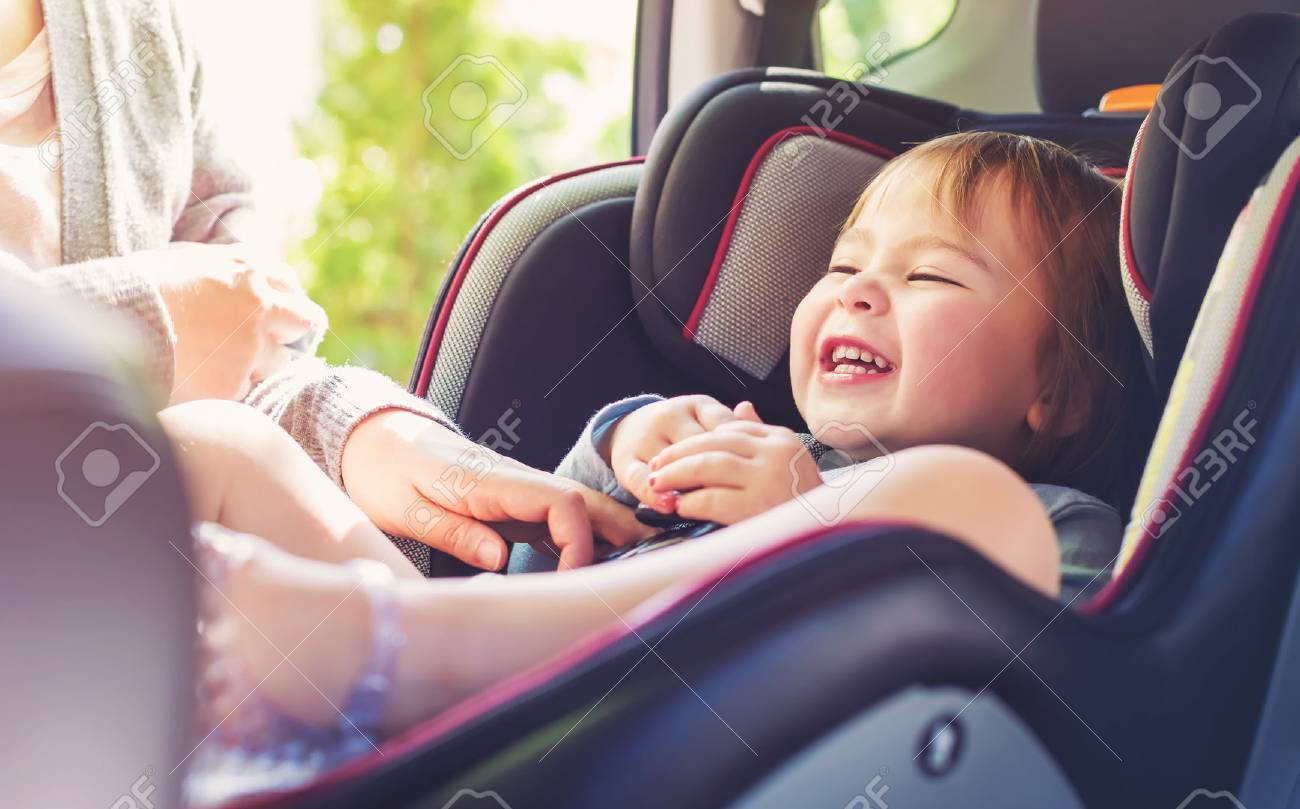 Toddler girl buckled into her car seat Standard-Bild - 60979489
