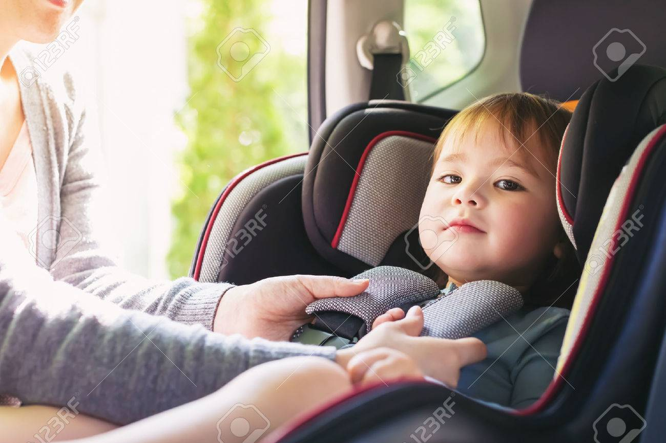 Toddler girl buckled into her car seat Standard-Bild - 60979495