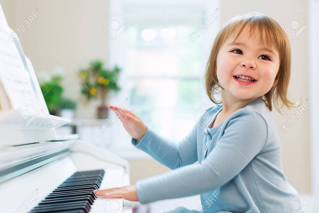 Happy smiling toddler girl excited to play the piano Standard-Bild - 64984137