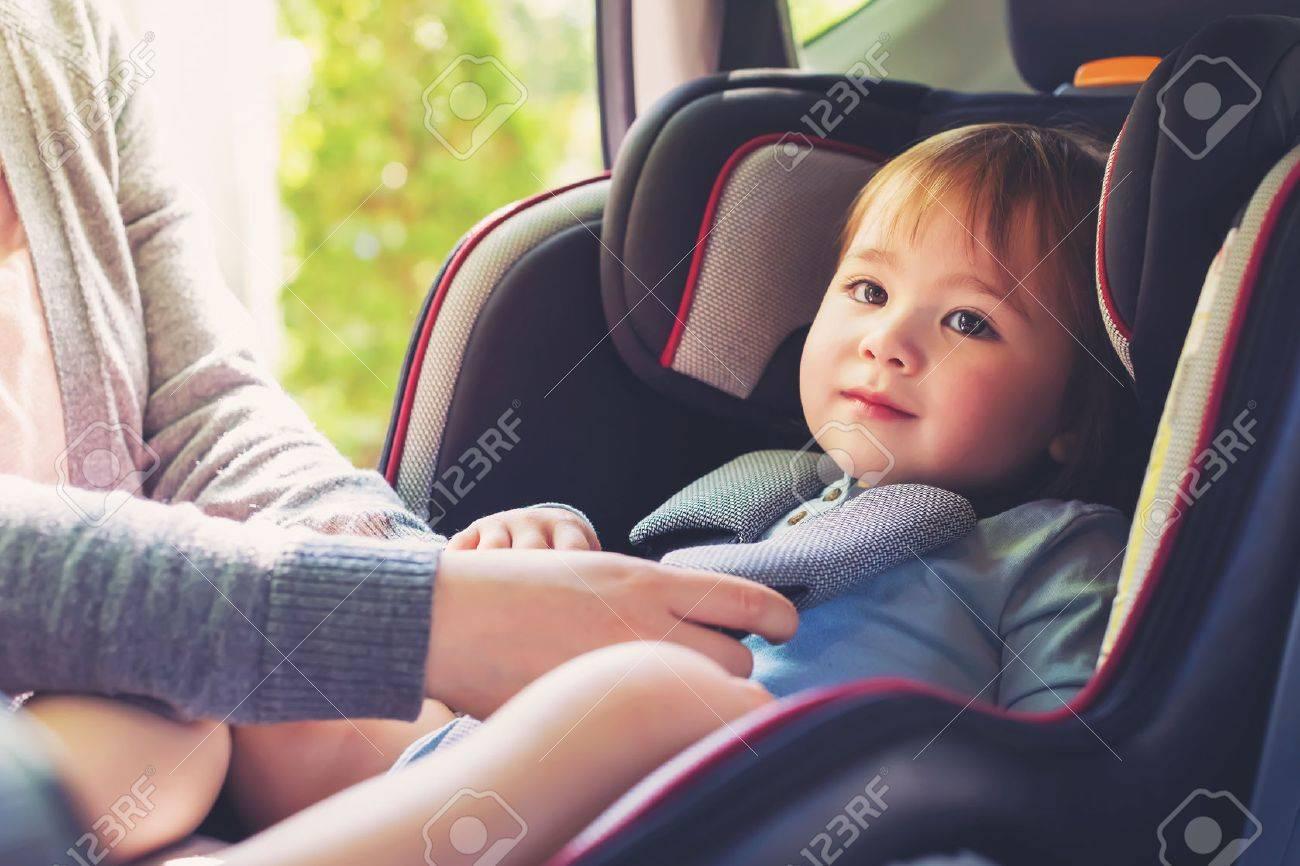 Toddler girl buckled into her car seat Standard-Bild - 60979510