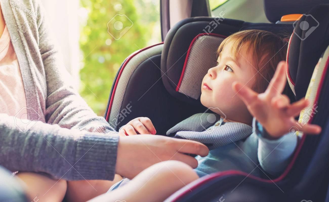 Toddler girl buckled into her car seat Standard-Bild - 60979523