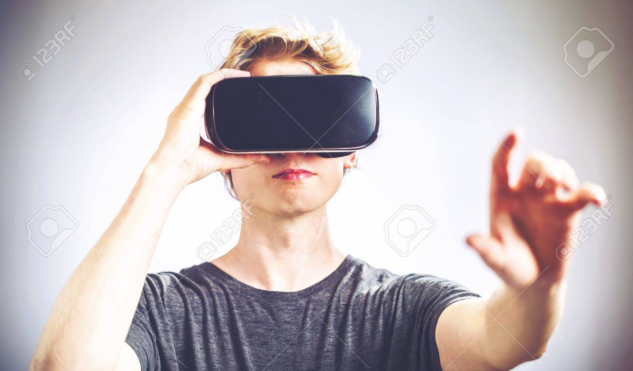 Blond man using a virtual reality headset Standard-Bild - 61514255