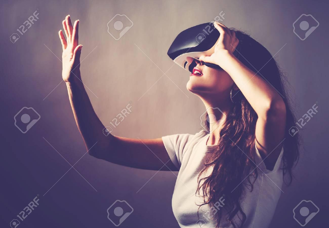 c88cc4ec3cca Stock Photo - Young woman using a virtual reality headset