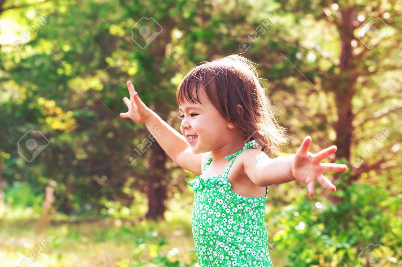 Happy smiling toddler girl playing outside Standard-Bild - 65011272