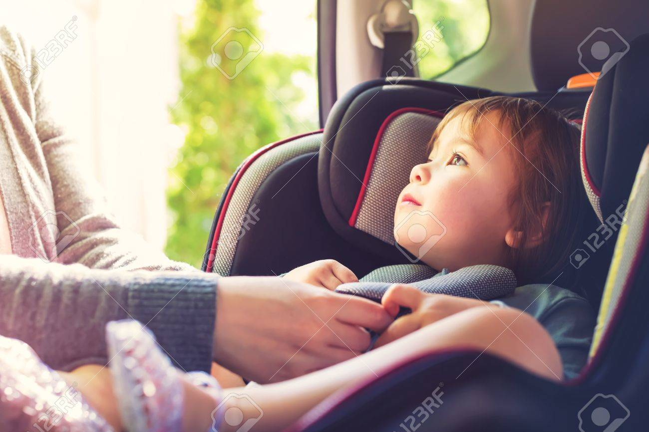 Toddler girl buckled into her car seat Standard-Bild - 73897173