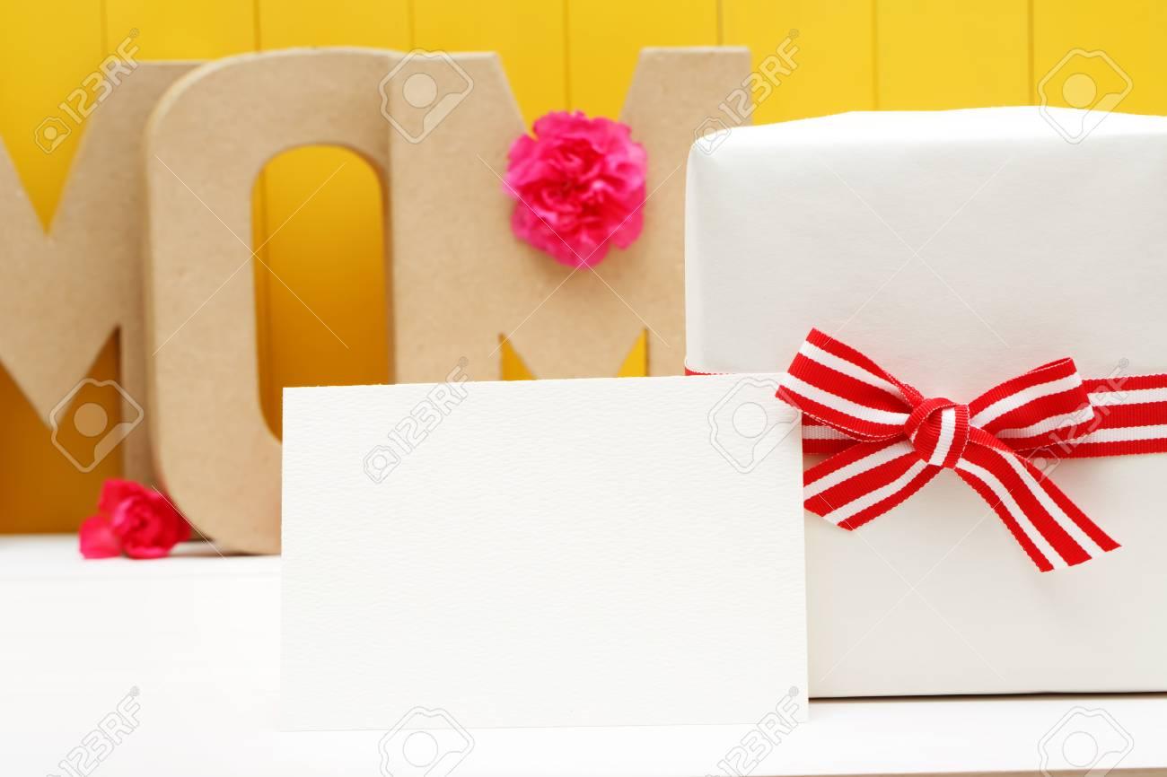 Blocs De Lettre De Maman Avec Une Boîte Cadeau Et Des Fleurs Doeillets Roses Sur Un Mur En Bois Jaune