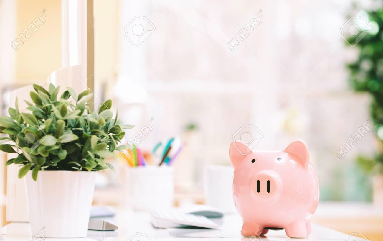 Pink piggy bank on a desk in an office - 77588632