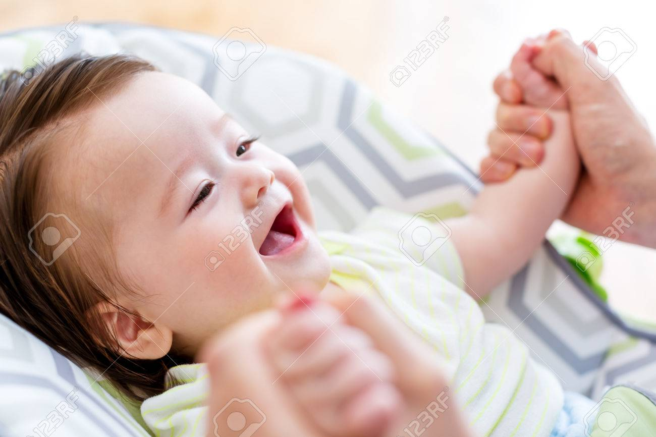Happy baby boy playing with his parent in his house - 81367501