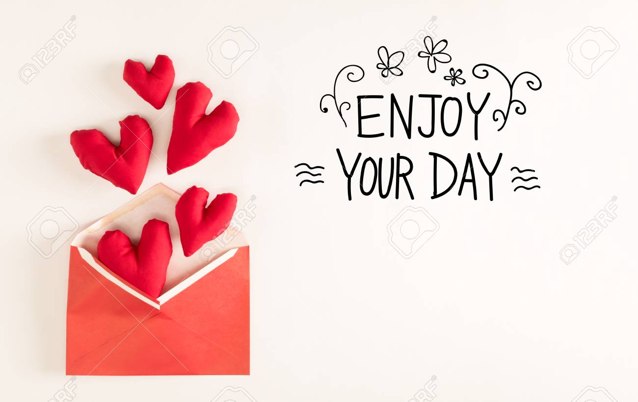 Enjoy Your Day Message With Red Heart Cushions Coming Out Of An Envelope  Stock Photo