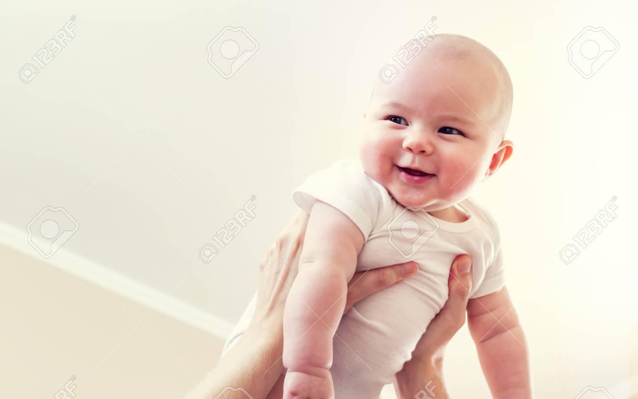Archivio Fotografico - Felice bambino neonato ragazza che si terrà in aria  dal suo genitore 7869e92f8ca8