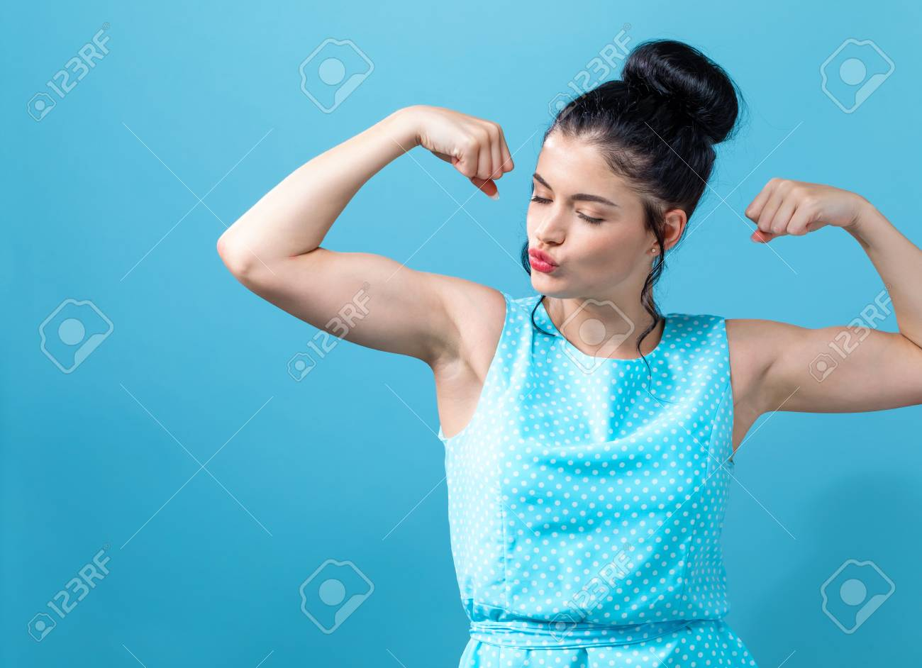 Powerful young woman in a success pose - 108316889