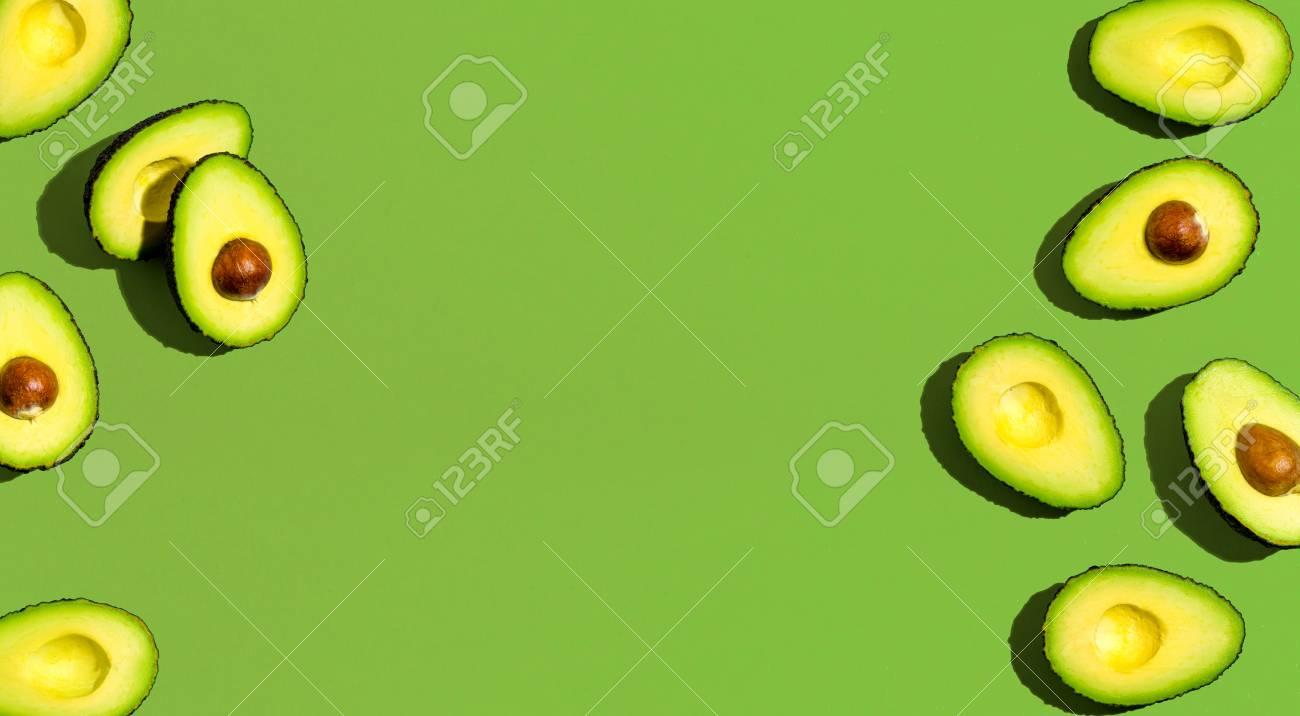 Fresh avocado pattern on a green background flat lay - 110707067