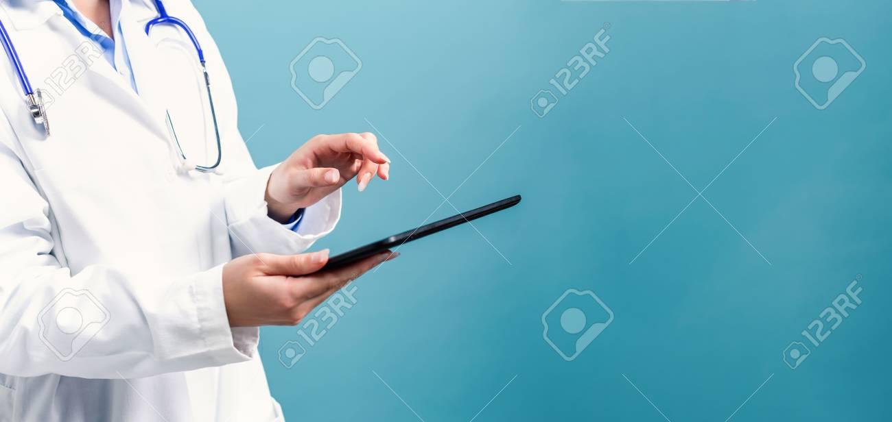 Medical doctor with digital tablet on a blue background - 111662334