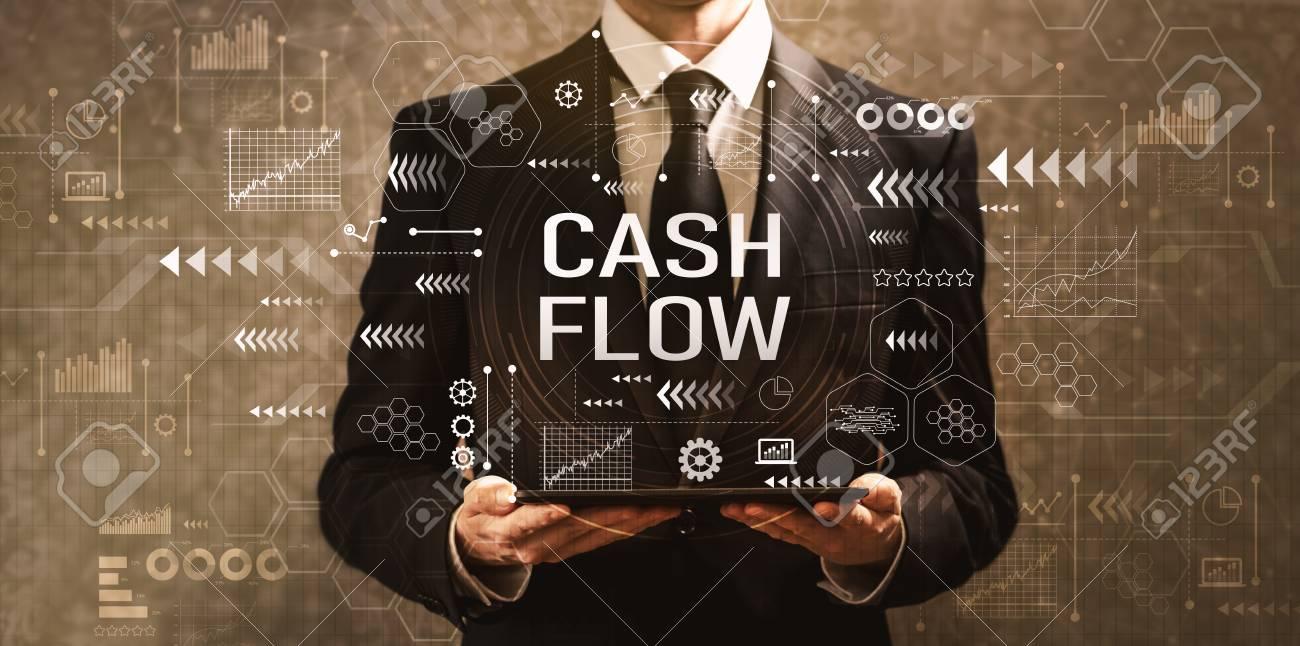 Cash flow with businessman holding a tablet computer on a dark vintage background - 111744685