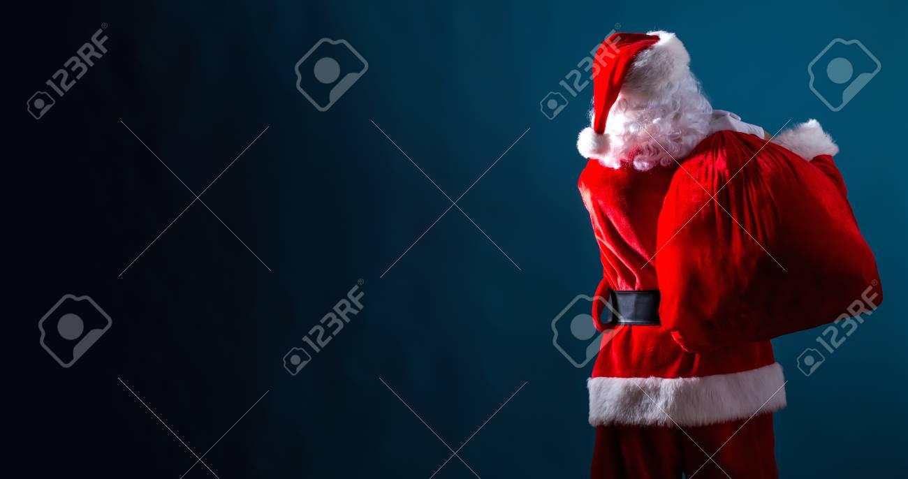 Santa holding a red sack on a dark blue background - 111825891