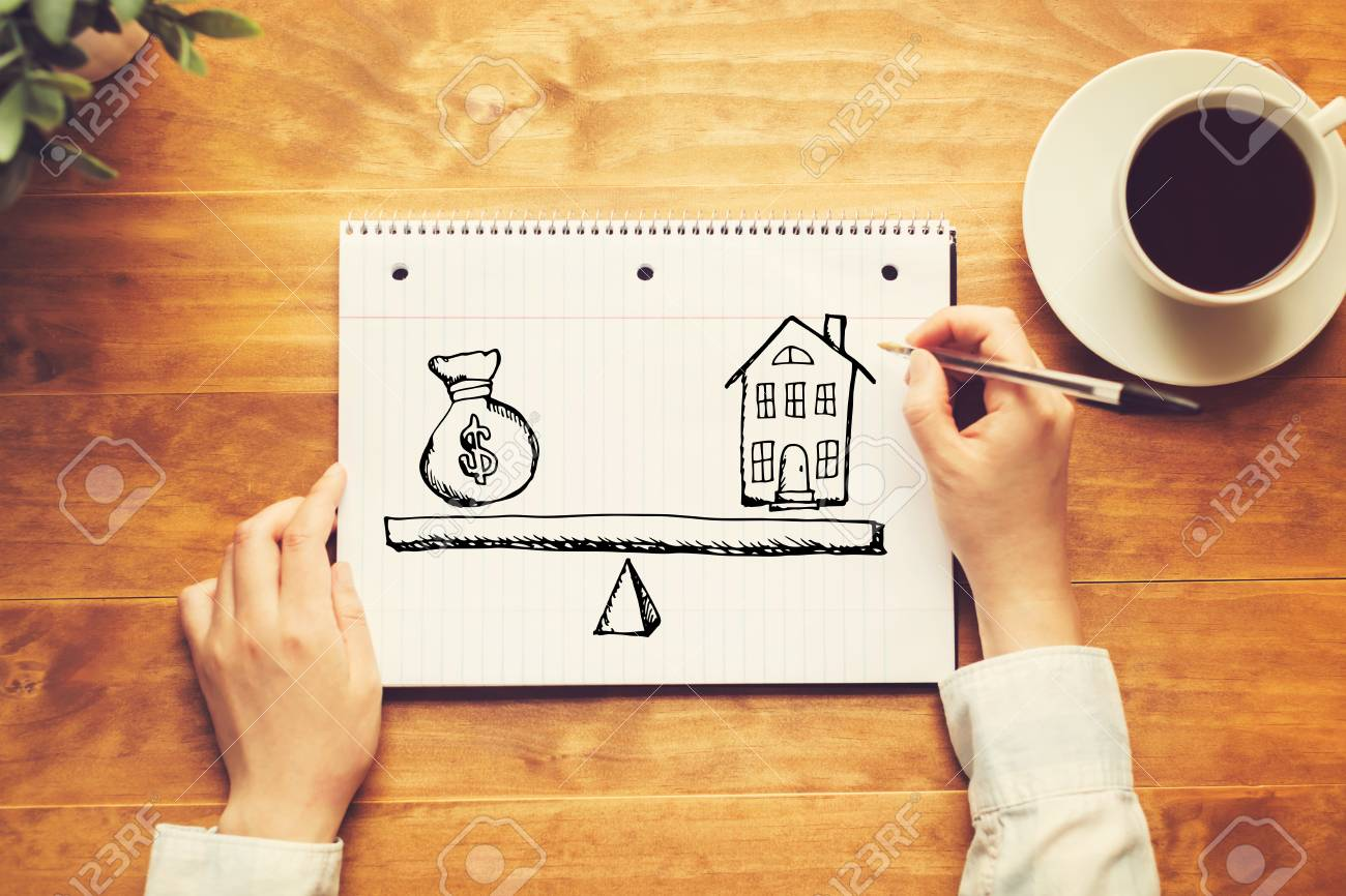 House and money on the scale with a person holding a pen on a wooden desk - 120268224