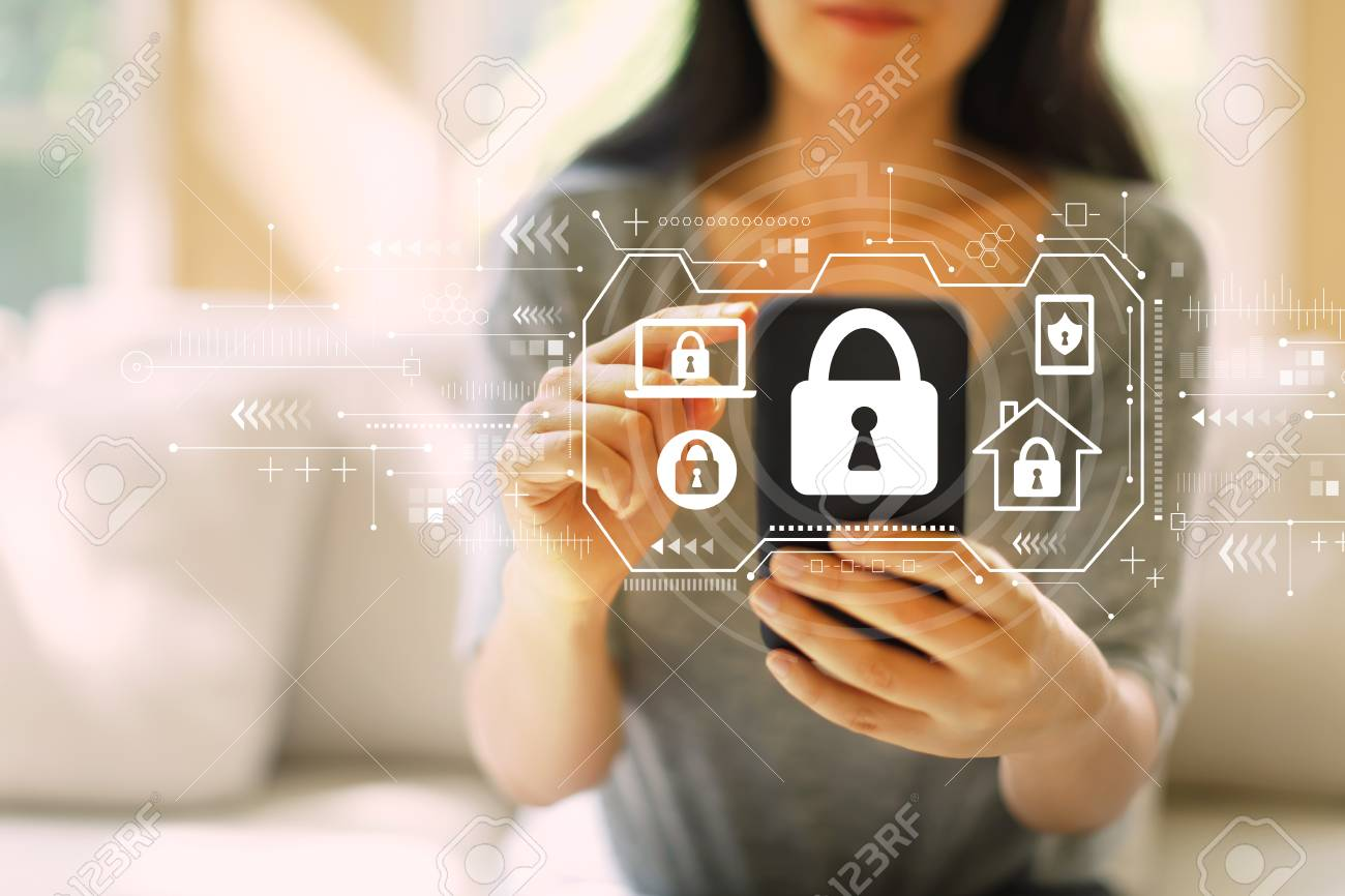 Security theme with woman using her smartphone in a living room - 121338449