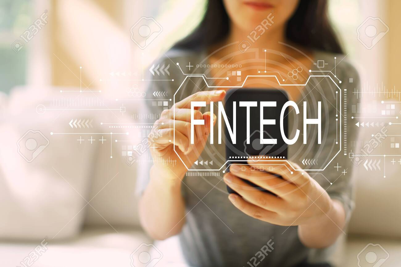 Fintech concept with woman using her smartphone in a living room - 121429299