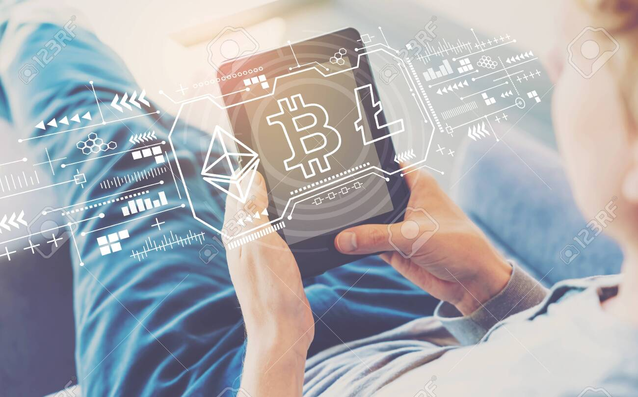 Cryptocurrency - Bitcoin, Ethereum, Litecoin with man using a tablet in a chair - 124813274
