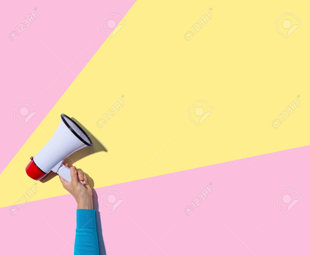 Person holding a megaphone with hard shadow - 129410577
