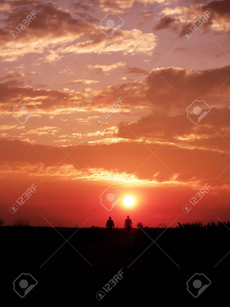 Two people running on the sunset with a sky full of clouds. Stock Photo - 2892382